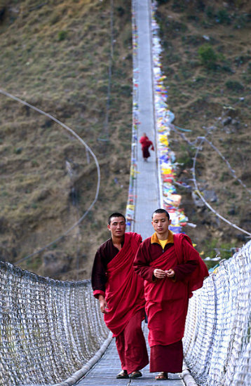 shobha gopinath Monks walking perfectly poised on a swaying suspension bridge, Punakha, Bhutan